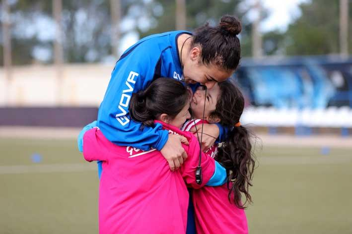 "Fun Coaching! Two young girls happily cling to their female football coach during the ""Live Your Goals Festival""   Copyright © Domenic Aquilina"