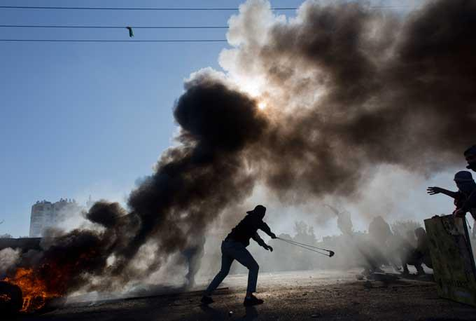 Palestinian protesters burn tires and clash with Israeli troops following protests against U.S. President Donald Trump's decision to recognize Jerusalem as the capital of Israel, in the West Bank city of Ramallah, Friday, Dec. 8, 2017.