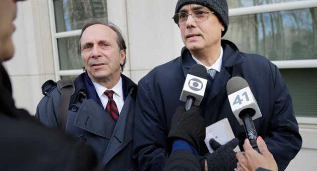 Manuel Burga, right, talks to reporters after leaving federal court in the Brooklyn borough of New York, Tuesday, Dec. 26, 2017