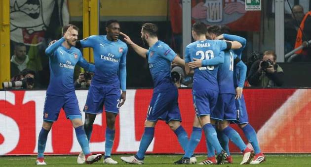 Arsenal's Aaron Ramsey, left, celebrates with teammates after scoring his side's second goal during the Europa League, round of 16 first-leg soccer match between AC Milan and Arsenal, at the Milan San Siro stadium, Italy, Thursday, March 8, 2018. (AP Photo/Antonio Calanni)