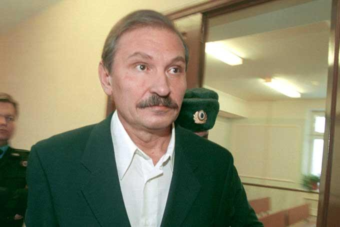 In this Tuesday, Dec. 19, 2000 file photo, ex-deputy director general of Aeroflot airlines company Nikolai Glushkov leaves the Lefortovsky court escorted by police officers, after the judge refused to release him on bail, in Moscow