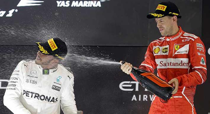 A Sunday, Nov. 26, 2017 file photo showing Mercedes driver Lewis Hamilton of Britain, left, and Ferrari driver Sebastian Vettel of Germany celebrating after the Emirates Formula One Grand Prix at the Yas Marina racetrack in Abu Dhabi, United Arab Emirates. Lewis Hamilton and Sebastian Vettel start the Formula One season within touching distance of further greatness. A fifth world title would move one of them level with Juan Manuel Fangio and second only to Michael Schumacher's seven. (AP Photo/Luca Bruno, File)